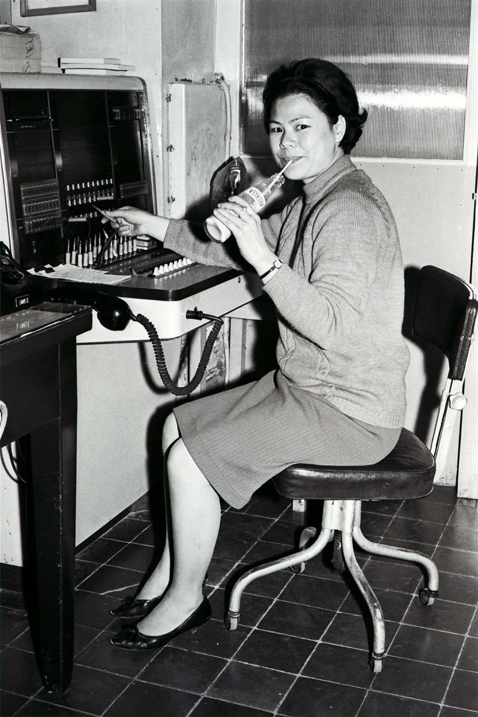 A switchboard operator at Vitasoy drinks a bottle of the company's soya milk in this picture from 1967. Photo: SCMP