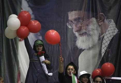 In front of a portrait of Iranian supreme leader Ayatollah Ali Khamenei, supporters of the presidential candidate Ali Akbar Velayati, a conservative former foreign minister, hold up balloons in a campaign rally, two days prior to the election, in Tehran, Iran, Wednesday, June 12, 2013.