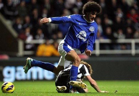Newcastle United's captain Fabricio Coloccini, below, vies for the ball with Everton's Marouane Fellaini, top, during their English Premier League soccer match at St James' Park, Newcastle, England, Wednesday, Jan. 2, 2013.