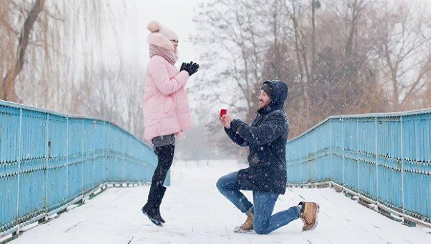 Молодой человек делает предложение руки и сердца своей девушке. Архивное
