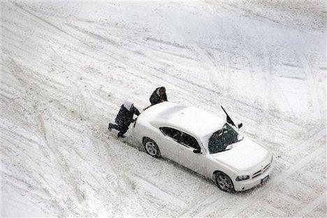 Two men help push a car down a snow-covered street Thursday, Feb. 21, 2013, in St. Louis.