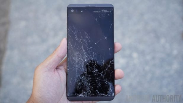 An LG V20 smartphone with a shattered screen held in a hand.