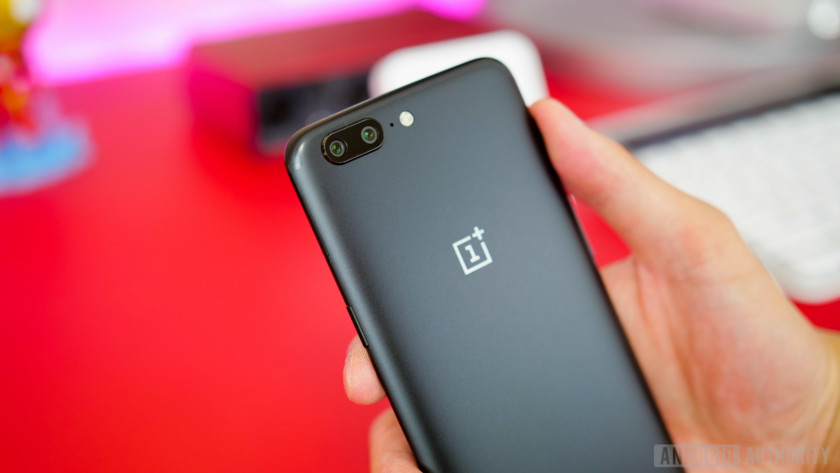The OnePlus 5 in black, held in a person's hand, showing its rear cameras.