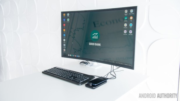 The Samsung Dex Pad on a white desk with a monitor and keyboard next to it.
