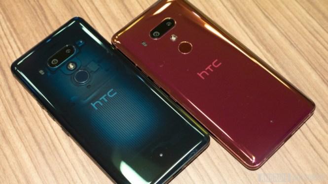 A blue HTC U12 Plus smartphone and a red HTC U12 Plus smartphone on a wooden surface.