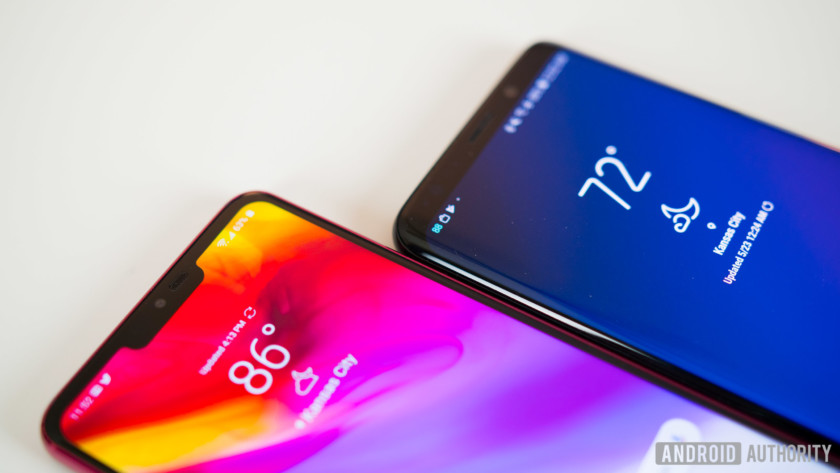 The LG G7 ThinQ and Samsung Galaxy S9 Plus, face-up on a white desk next to each other.