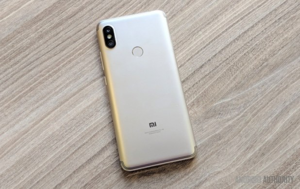 Xiaomi Redim Y2 smartphone with a gold back, face-down on a wooden desk.