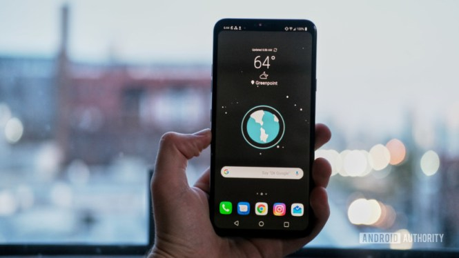 LG V40 ThinQ in hand showing home screen