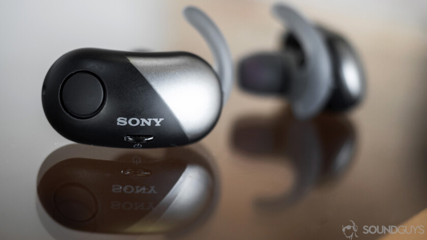 Sony WF-SP700N true wireless iPhone earbuds resting on glass surface.