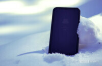 A cold phone half-buried in some white snow.