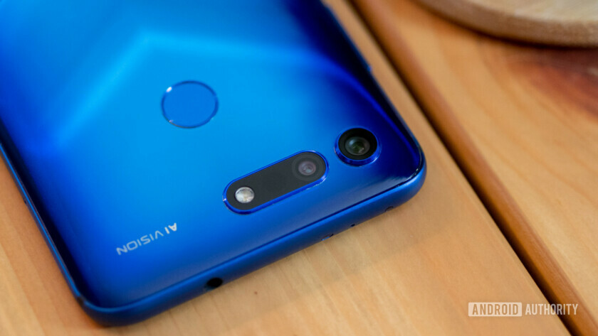 Honor View 20 in Blue on a wooden table, only half in shot.