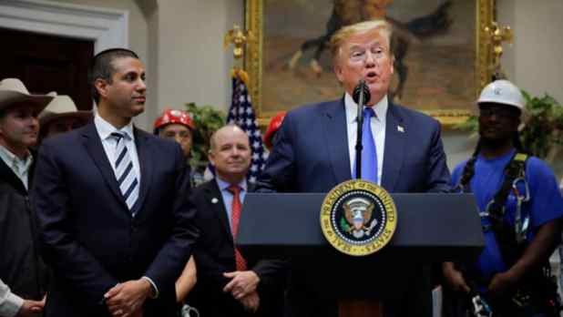 President Donald Trump standing at a press podium next to FCC chairman Ajit Pai as Trump delivers a speech about 5G plans for the United States.