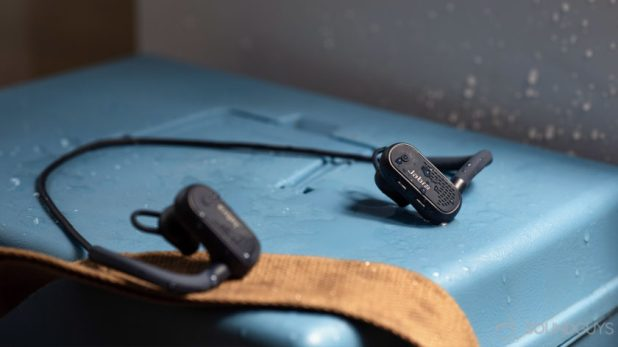 The earbuds covered in water on a blue surface.