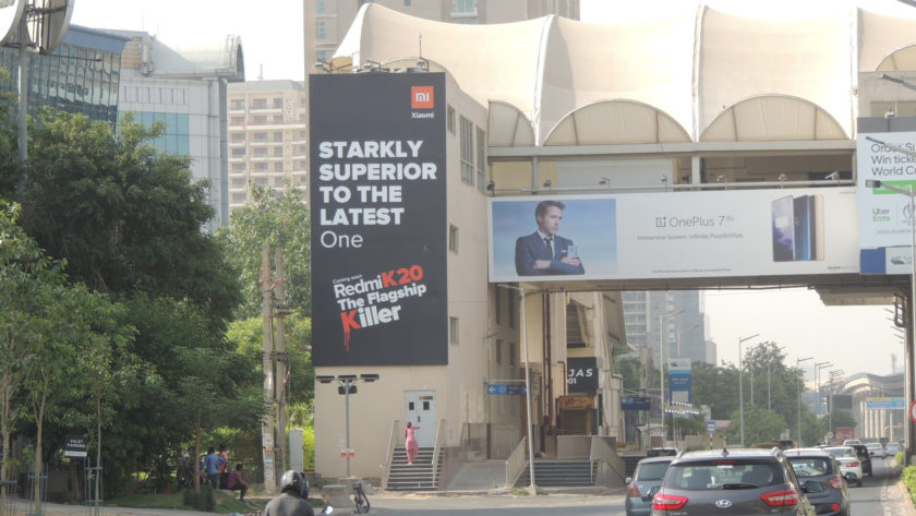 An image of two competing billboards for the smartphone companies Redmi and OnePlus.