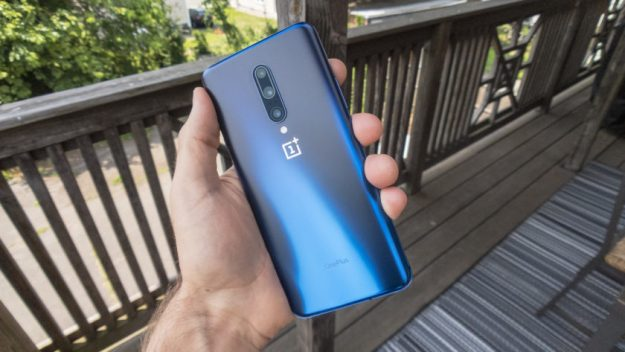 A hand holding a OnePlus 7 Pro so that you can see the back, which is the Nebula Blue color.