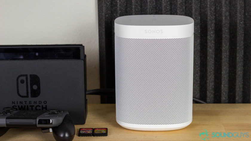 Sonos One best Alexa speaker in white next to a Nintendo Switch stand with game cartridges in front. The items are on a wood desk with soundproof foam in the background.