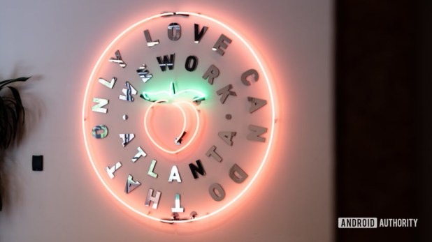 A neon sign welcoming visitors to WeWork in Atlanta. It has a peach in the center.
