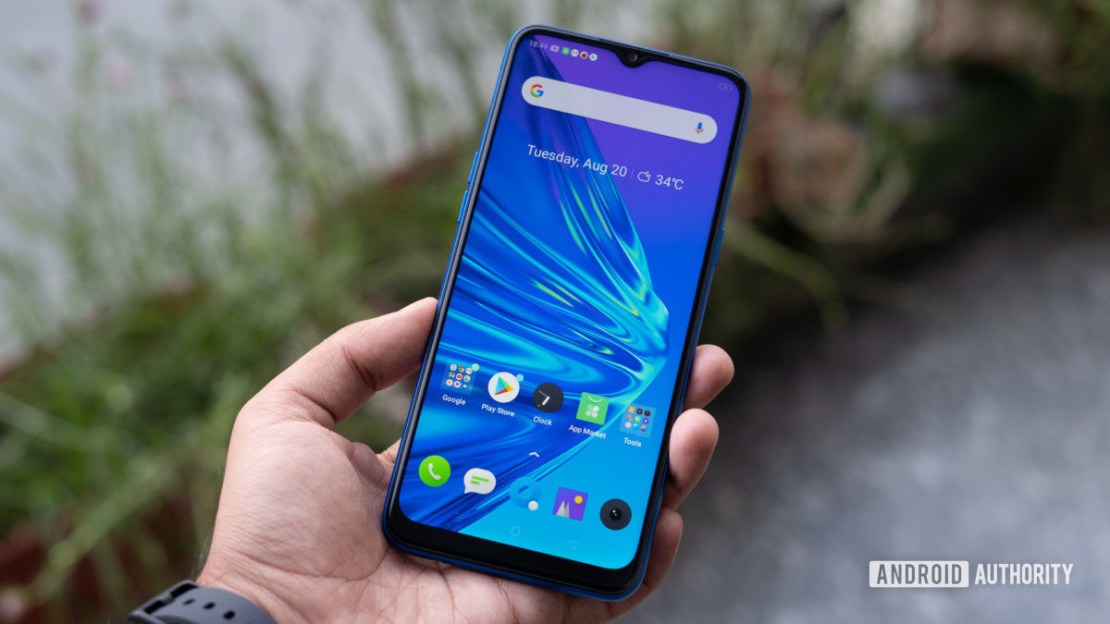 Realme 5 in hand showing display and homescreen
