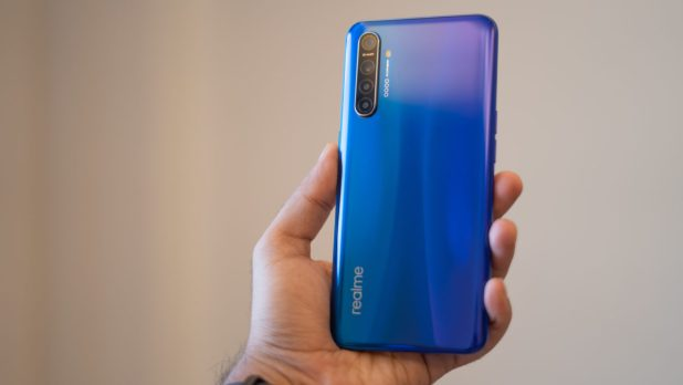 Realme XT in hand with back panel and gradient