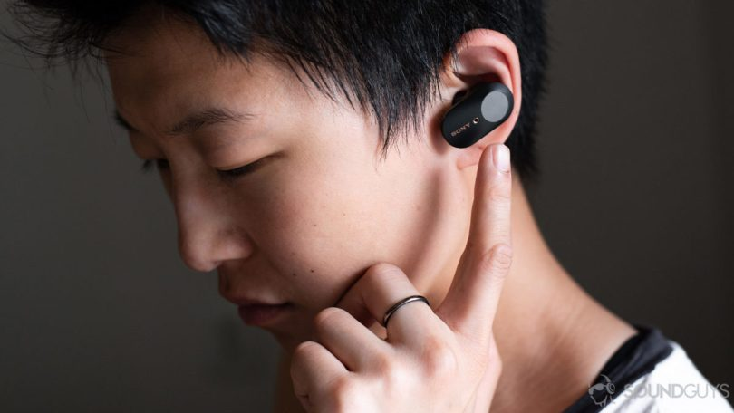 A woman wears the Sony WF-1000XM3 earbuds and reaching for the touch panel of the left 'bud.