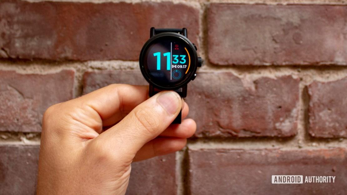 Misfit Vapor X Smartwatch Held in Hand Against Brick Wall