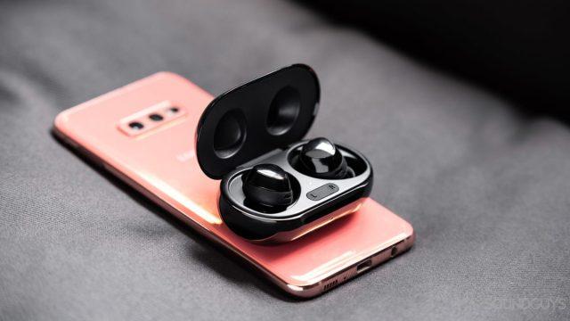 A photo of the Samsung Galaxy Buds Plus true wireless earbuds using wireless PowerShare atop a Samsung Galaxy S10e.