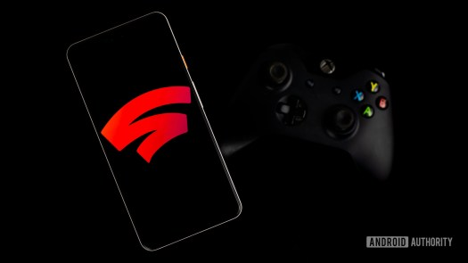 Google Stadia on smartphone next to gaming controller stock photo 1