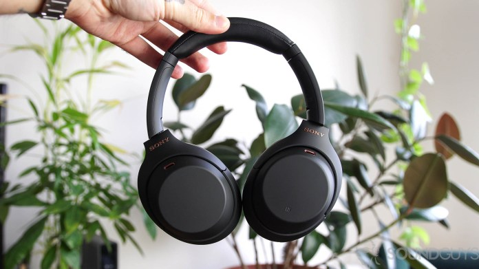 A photo of the Sony WH 1000XM4 noise cancelling headphones held by a man in front of indoor plants.
