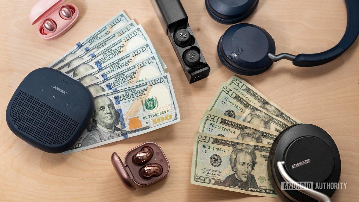Образ денег в окружении беспроводных аудиопродуктов, таких как динамик Bose SoundLink Micro, Samsung Galaxy Buds Live, 1More Colorbuds, Jabra Elite 45h, JBL True Wireless Flash X и Shure AONIC 50.