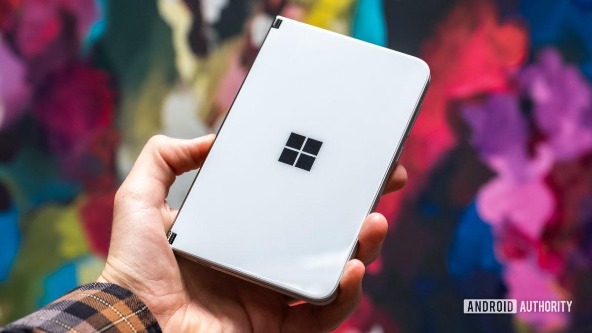 Microsoft Surface Duo fechado na mão contra o fundo