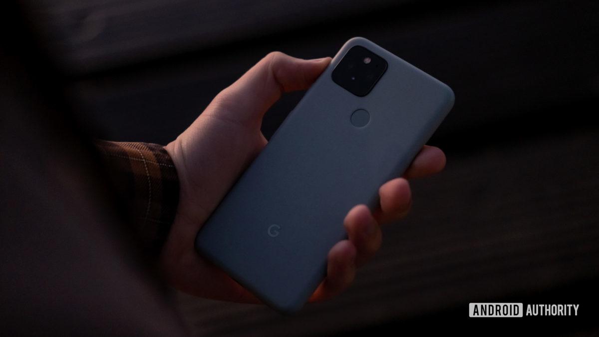 Google Pixel 5 держит в руке экраном вниз 1