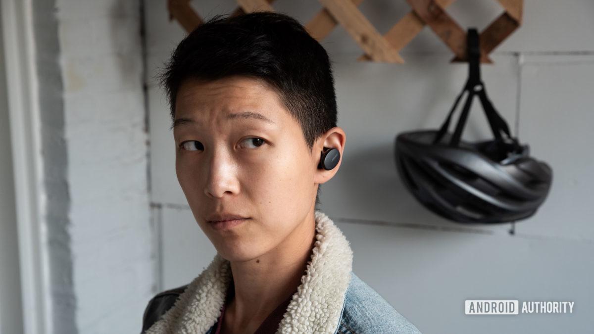Uma mulher usa os verdadeiros fones de ouvido sem fio Bose Sport Earbuds com um capacete de ciclismo ao fundo.