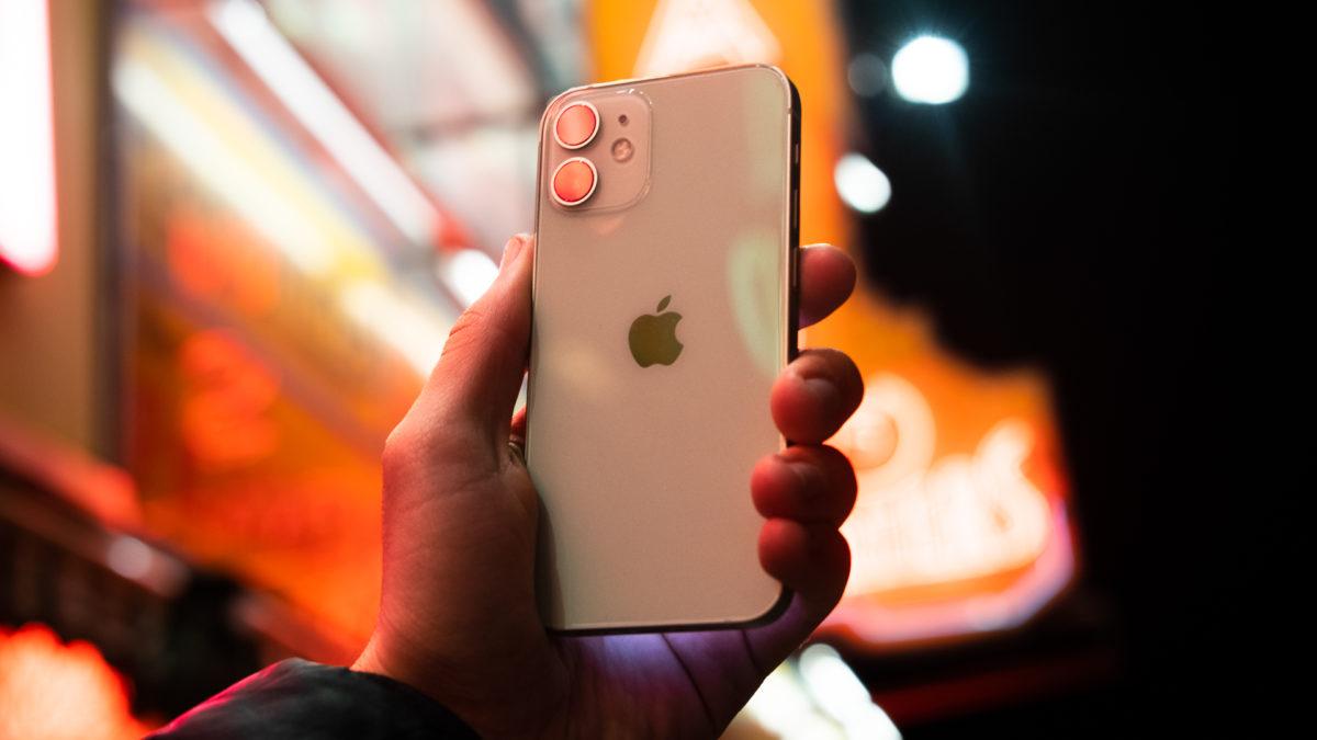 iPhone 12 Mini на задней панели телефона перед неоновой подсветкой - проверьте, сколько лет вашему телефону