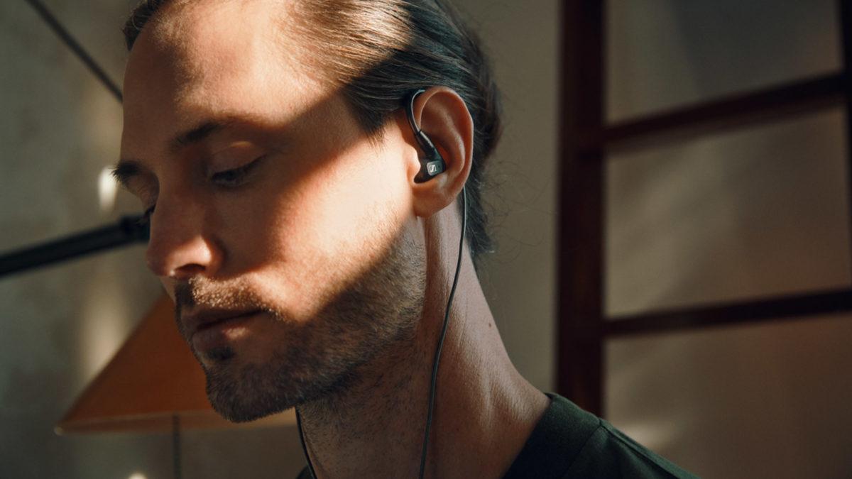 Um homem usa fones de ouvido Sennheiser IE 300