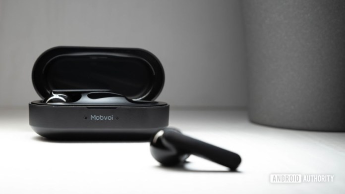 The Mobvoi Earbuds Gesture true wireless earbuds case open with a blurred out earbud in the foreground.