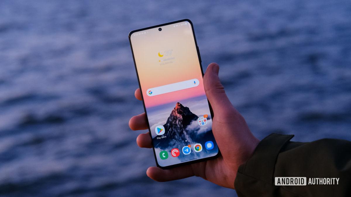 Дисплей Samsung Galaxy S21 Ultra в руке над водой