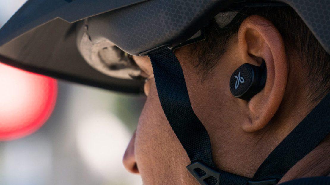 A man wears the Jaybird Vista 2 true wireless workout earbuds while cycling.