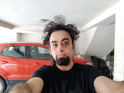 The OnePlus Nord primary selfie indoors of a man with black hair and a beard, wearing a black t-shirt and standing in front of a red vehicle.