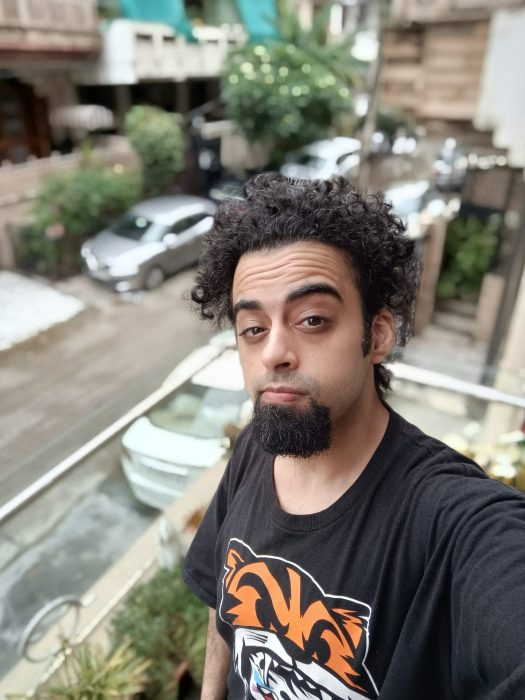 The Oppo Reno 6 Pro selfie portrait mode showing a man with black hair and beard in a black t-shirt with orange pattern standing on a balcony above the street below.