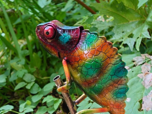 Sony Xperia 1 III camera 70mm shot of a colorful metal chameleon garden ornament in front of green leaves.