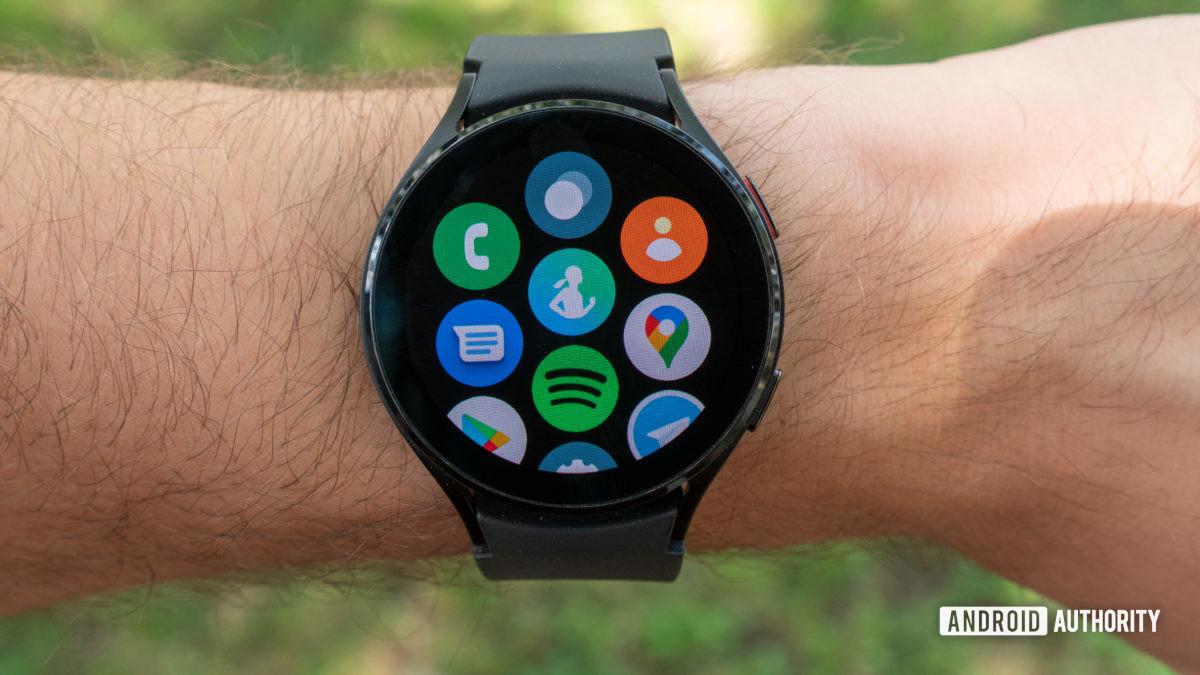 Samsung Galaxy Watch 4 на мужском запястье со страницей всех приложений.