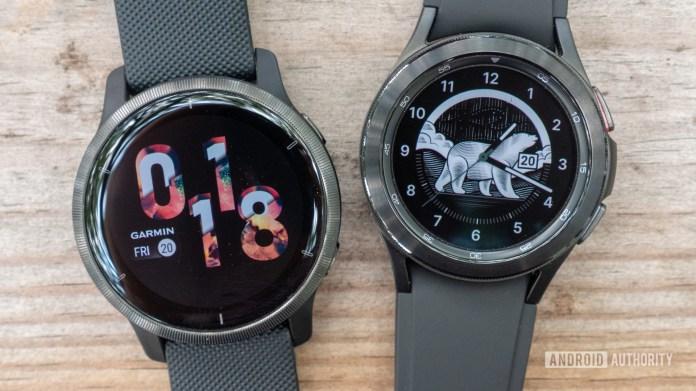 The Samsung Galaxy Watch 4 Classic and Garmin Venu 2 lying flat on a table.