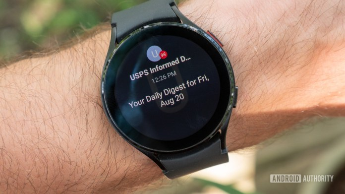 The Samsung Galaxy Watch 4 on a wrist showing the Gmail notification.