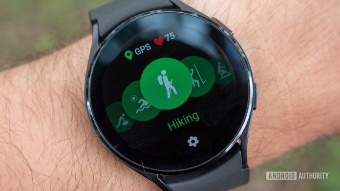 The Samsung Galaxy Watch 4 on a wrist showing the hiking workout mode with GPS and heart rate icons.