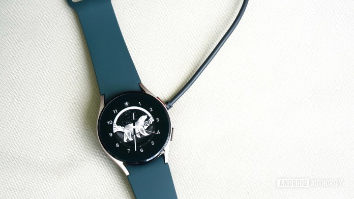 A Galaxy Watch 4 rests on a cream linen surface, charging with a replacement charging cable.