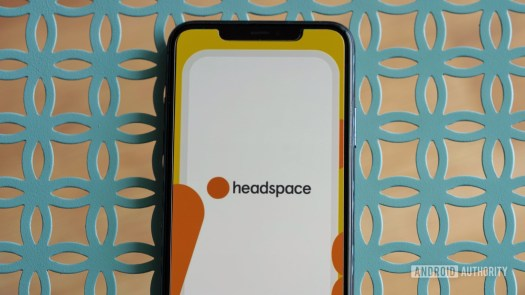 An iPhone 11 rests on a teal metal table, displaying the Headspace app logo.