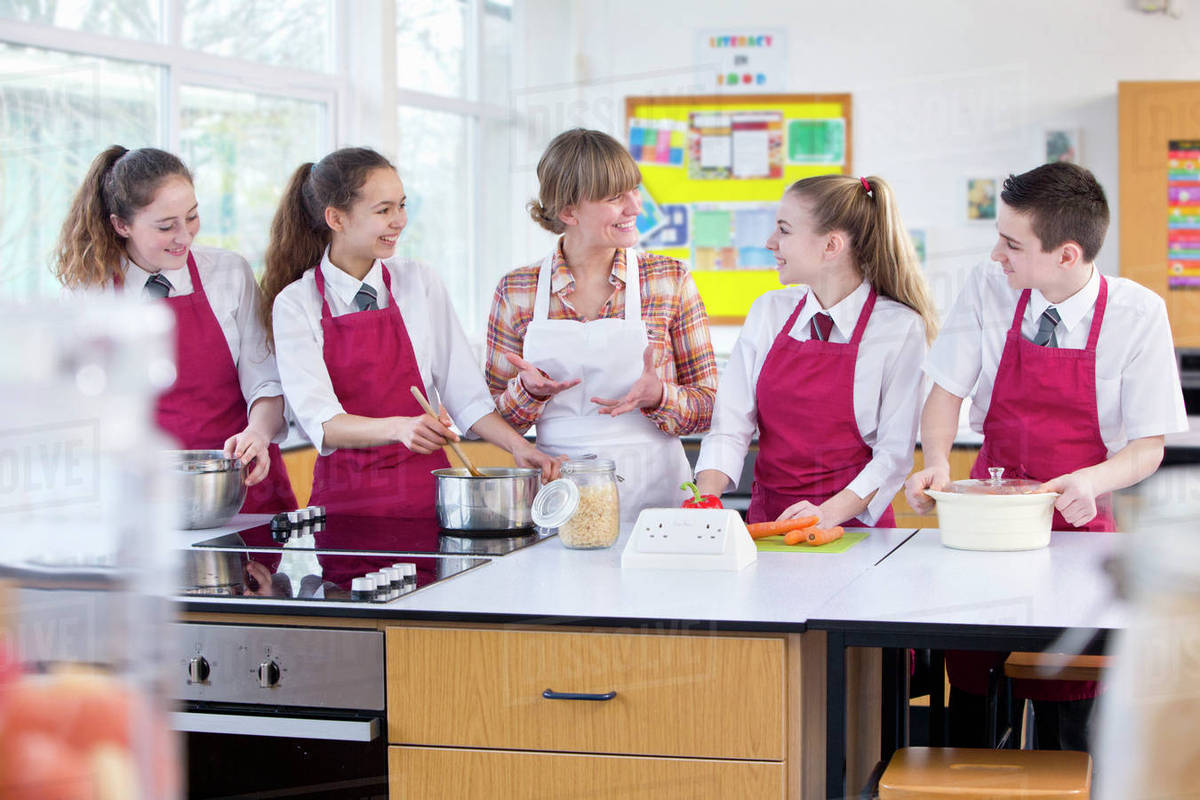 Teacher Guiding High School Students Cooking In Home