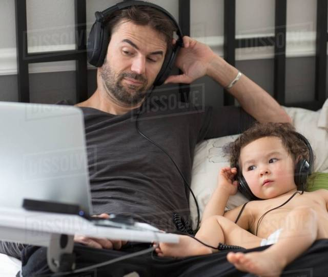 Father And Toddler Daughter Reclining In Bed Listening To Music On Headphones