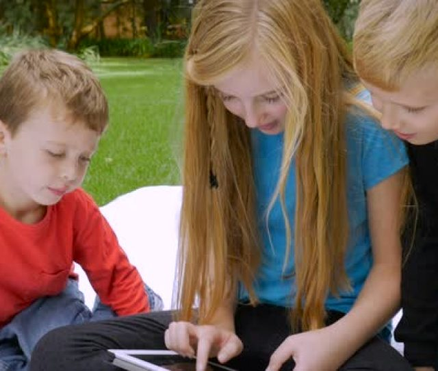 Three Young Cute Adorable Children Are Completely Engaged On Their Shared Tablet Slow Motion