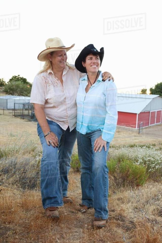 Mature Lesbian Couple Standing Together On Ranch Smiling